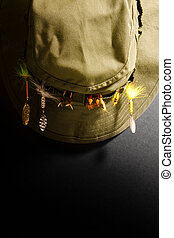 Fishing hat with lures against a black background