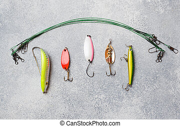 Fishing hooks and baits in a set for catching different fish on a grey background with copy space. Flat lay
