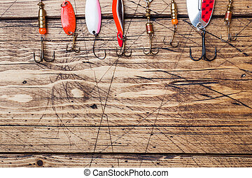 Fishing hooks and baits in a set for catching different fish on a wooden background with copy space. Flat lay