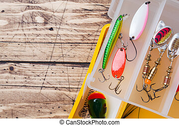 Fishing hooks and baits in a set for catching different fish on a wooden background with copy space.