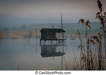 Fishing house on the water in the morning fog