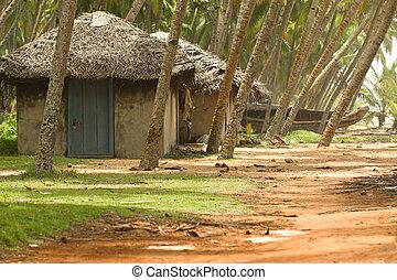 Fishing huts in Kerala India with fishing boat in the ...