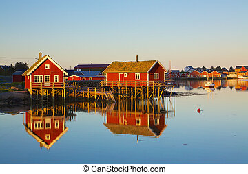 Typical red rorbu huts with sod roof in town of Reine on Lofoten islands in Norway lit by midnight sun
