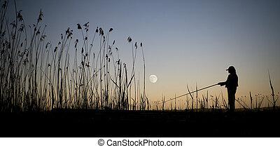 Fishing in moonshine - Person fishing in moonshine