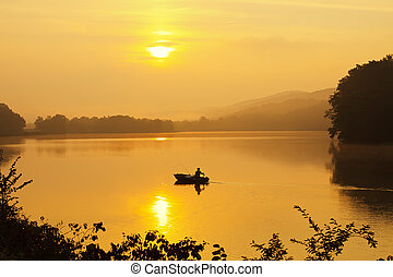 Fishing in Morning Fog - A lone fisherman moves out on a ...
