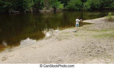 Fisherman with a fishing rod on the river bank. Man...