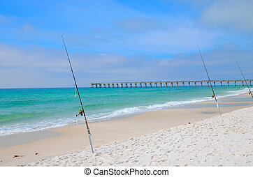 Fishing poles in the sands of a Panama City FL beach, Pier in the background