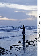 Fishing in the Sea - A man fishing in the ocean at dusk.