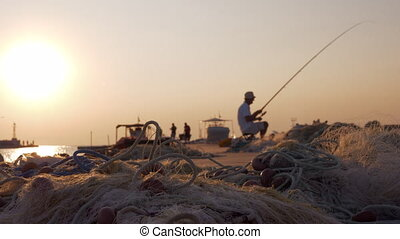 Fishing in the small quay at sunset