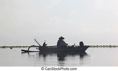 Fishing   - Indonesian man sitting on boat and fishing