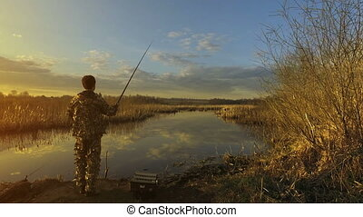 Fishing intro fisherman, man throw a fishing rod into the pond or lake, evening sunset, warm, yellow fish titles text, camera move, ultra HD