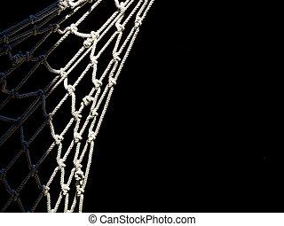 Fishing net hanging, detail. Black background. - Sunlit.