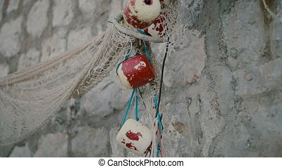 Fishing net, ropes and fishing lamp on a stone wall on the beach