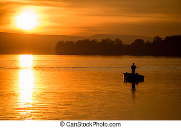 Fishing on a boat at sunset
