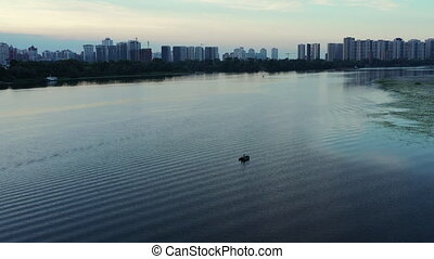 Fishing boat with an angler in the middle of a riverbed in the city in the morning near the City. Drone shot.