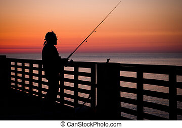 Fishing Pier - Fishing in the ocean from a pier in early...