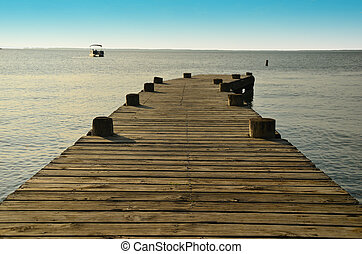 Fishing pier on the lake with a boat in the background.
