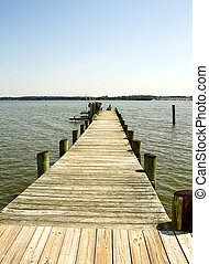Fishing pier with people sitting at end of it fishing