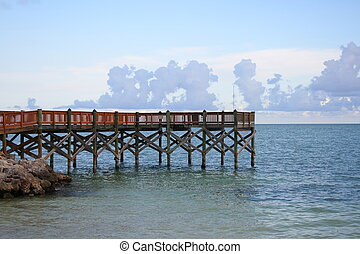 Long fishing pier over the ocean in the late afternoon