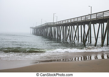 The Virginia Beach fishing pier with a sandy beach in the foreground on a foggy morning.