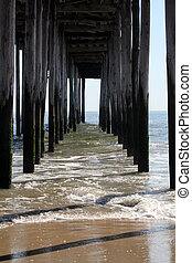 The waves roll beneath a fishing pier in Ocean City, Maryland