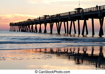Sunrise at a fishing pier on the ocean
