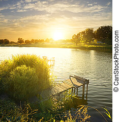 Wooden fishing pier by the river at sunrise