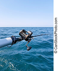 fishing pole over water - fishing rod and reel over Lake...