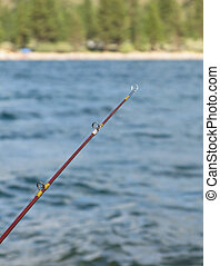 Fishing Pole - Fishing pole with water, shore and trees in...