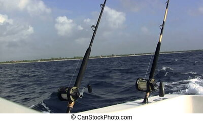A pair of fishing poles are bobing up and down in heavy seas trolling for fish.