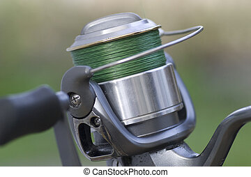 A silver grey fishing reel very close up with green line