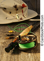 Fishing reel and hat on bench