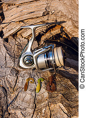 Fishing reel and various kind of baits on the natural background.