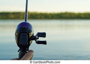 Closeup of a fishing reel casting over a lake