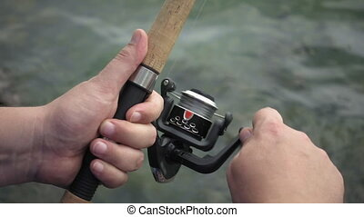 Fishing reel closeup slow motion. Man is fishing with...