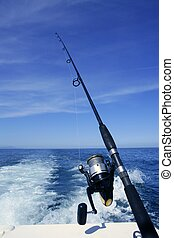 Fishing rod and reel on boat, fishing in blue ocean - ...