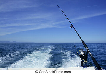 Fishing rod and reel on boat, fishing in blue ocean -...