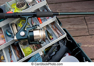 A fishermans rod reel and tackle box filled with lures and bait ready for the start of fishing season.
