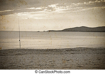 fishing rod by the sea in vintage tone