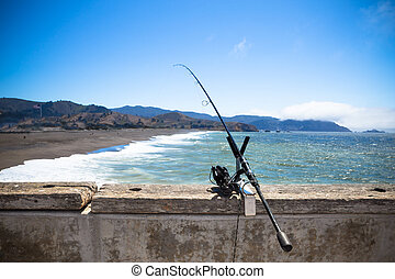 Fishing pole and reel along pier with ocean and coastal beach in the background