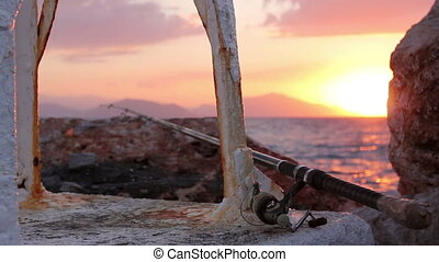 Fishing rod on a concrete at purple sunset - Fishing pole on...