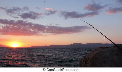 Fishing rod on a rock at purple sunset