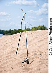 Fishing rod on the bank of the river on a background of blue sky