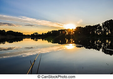 Fishing rod on the lake in sunset evening time.