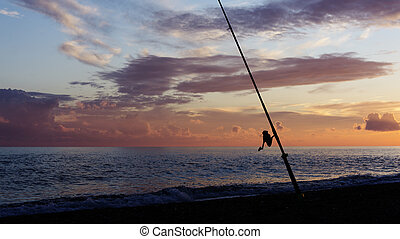 Fishing rod silhouette on the beach at sunset