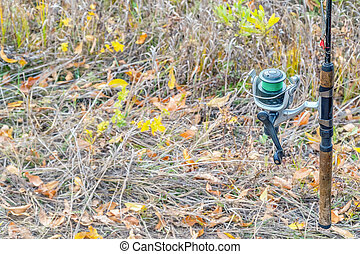 Fishing rod with a coil on the background of autumn grass