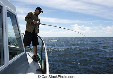 Fisherman holds a fishing rod during fishing safari.