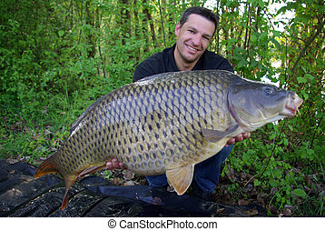 fishing scene. common carp - Catch of fish. Happy fisherman...