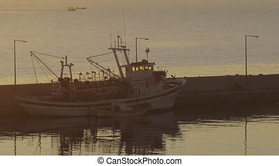 Fishing ship at anchor in sunset