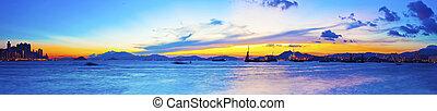 Fishing ship at sea with sunset along Hong Kong coastline